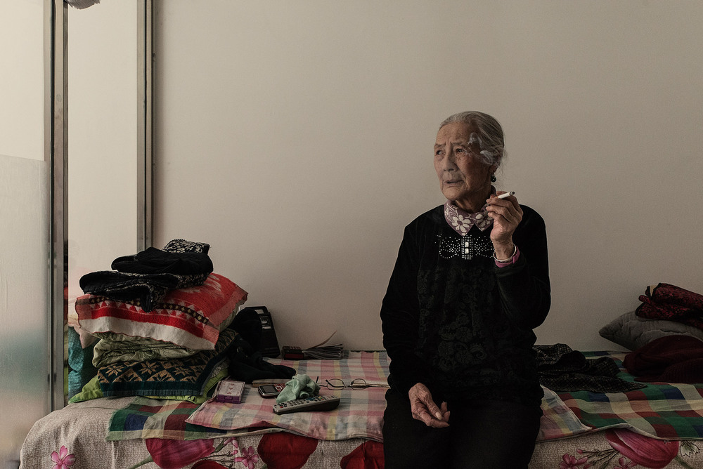 75 years old, Dushaocai sitting on her bed smoking, in Jarud Banner (Inner Mongolia). Dushaocai had to leave her grassland in Holingol due to pollution from a nearby aluminium mill. She was forced to resettle in an urban area, separated from her sons. Remembering her life on the grassland brings her to tears. Her best memory of, it is waking up before sunrise and cooking milk tea for her sons. Mongol nomads have been the first to be affected by forced resettlement, and wandering pastoralism a pillar of mongol culture and lifestyle, amost entirely disappeared in the 90s.