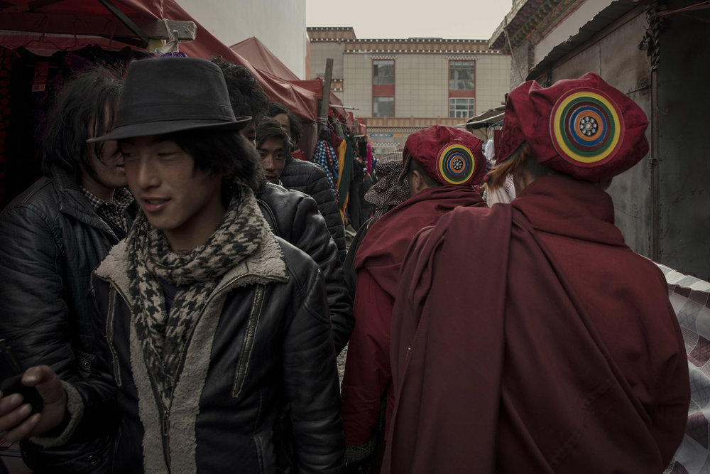 Young Tibetans crossing paths with Buddhist monks in Yushu (Qinghai) a market town for nomads of the region. For many of the younger generation of Tibetans, urban life is more appealing than the nomadic lifestyle of their parents however they remain attached to it. Nomadism and Buddhism are two main pillars of the Tibetan culture.