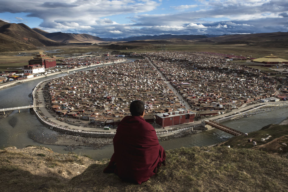 """A Buddhist monk looking out on the Yarchen Gar nunnery in China, where thousands of nuns live in makeshift huts.  Yarchen Gar is the second-largest """"gar,"""" which means monastic encampment in Tibetan. The biggest is Larung Gar, a couple of hundred km to the North East."""