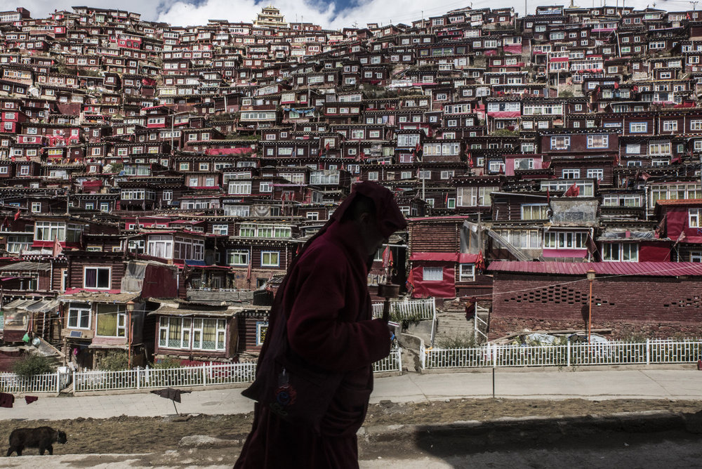 A Buddhist nun with a prayer wheel in Larung Gar, the largest monastic camp in Tibet. The thousands nuns and monks of Larung Gar live in small wooden huts.   Larung Gar has become one of the most influential institutions in the Tibetan world, the teachings of its senior monks praised, debated and proselytized from here to the Himalayas. Now Chinese officials are tightening control over the settlement, in what many Tibetans and their advocates call a severe blow to Tibetan religious practice.