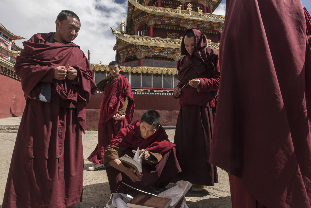Monks checking religious books for sale on the street.  Larung Gar has also become one of the most influential centers in the Tibetan world.