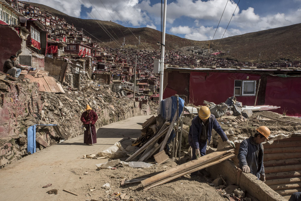 Workers dismantling a dwelling in Larung Gar. Residents and rights groups say officials intend to reduce the settlement's population to 5,000 by late next year through mass evictions.Hundreds of Buddhists had already been forced out of the area.