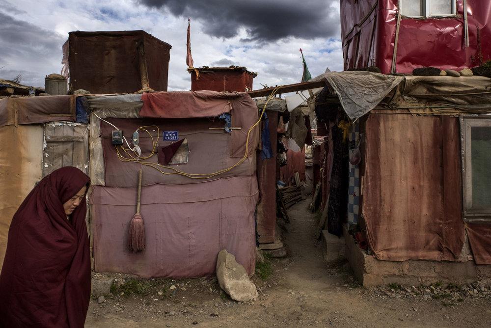 A nun walking past makeshift huts, living quarters for thousands Yarchen Gar nuns.