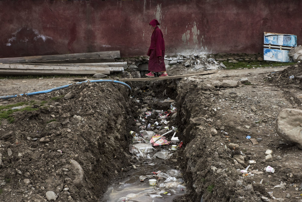 A nun walking on a plank over an open air sewage in Yarchen Gar. Sanitary conditions are extremely poor in both Larung Gar and Yarchen Gar. Cholera and typhoid outbreaks are a daily threat.