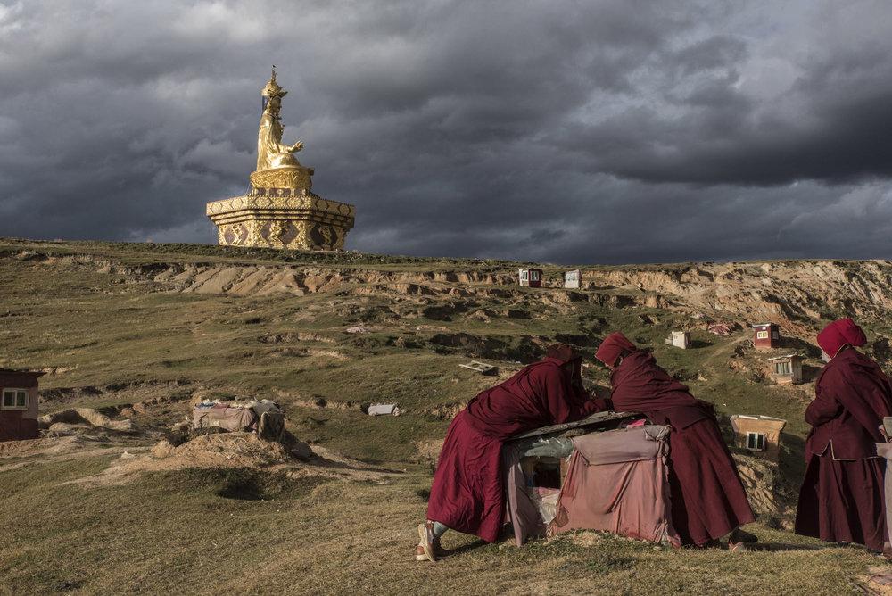 Nuns chatting near a giant statue of Padmasambhava, an Indian Buddhist master.