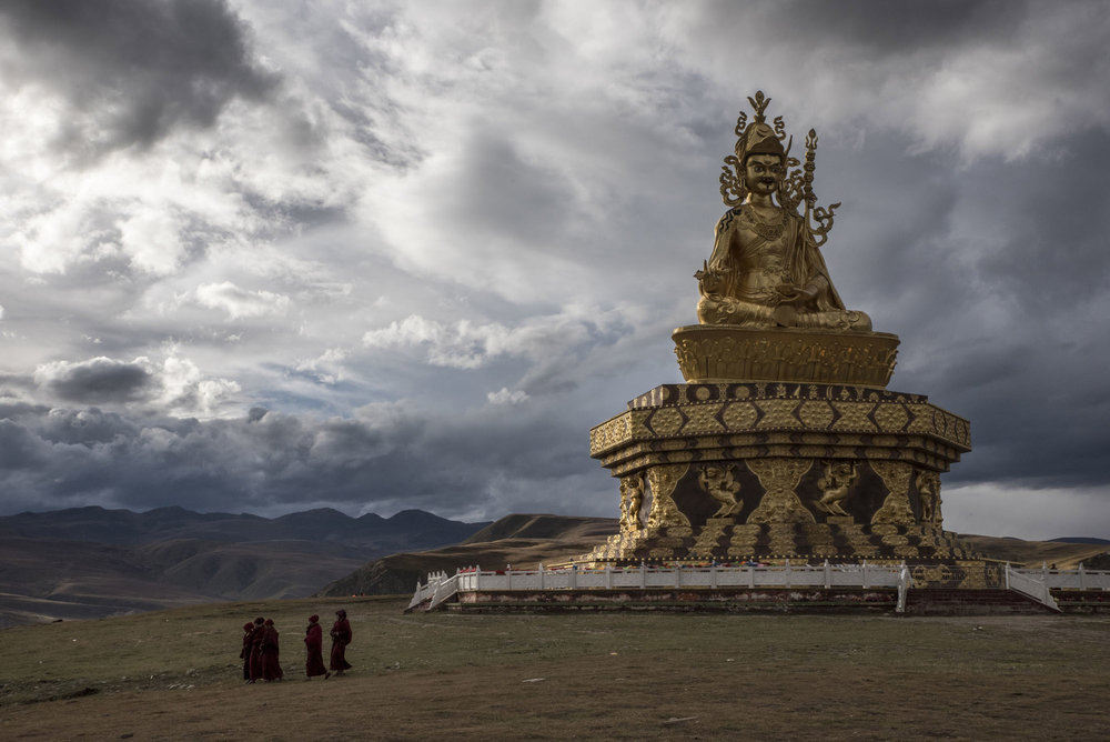 Nuns walking past a giant statue of Guru Rinpoche in Yarchen Gar. Vast amounts of money are being funnelled into gigantic, ornate temples and monuments, while the slum continues to crumble. Han Chinese money has poured into this region, with relatively wealthy converts to Tibetan Buddhism bringing much-needed funds to the camps.