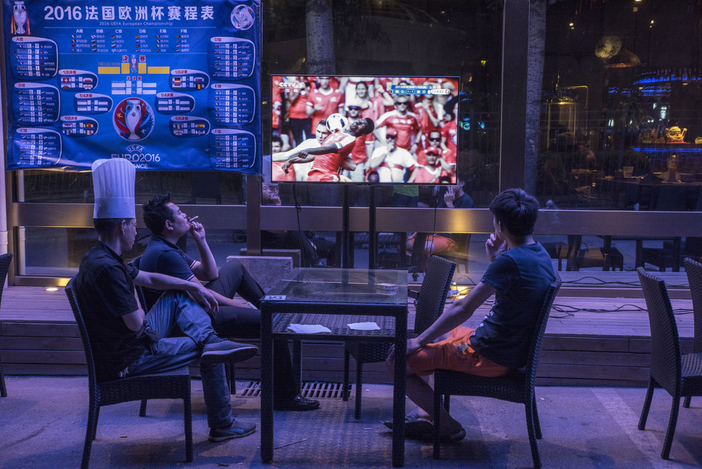 A cook and friends watching a game of the 2016 Eurocup, late at night on a street of Beijing. International football tournaments draw huge audiences in China, in spite of the absence of the National team which poor performances don't allow a presence in such games. The national men's team recently placed 83rd in FIFA rankings, just ahead of the Faroe Islands.