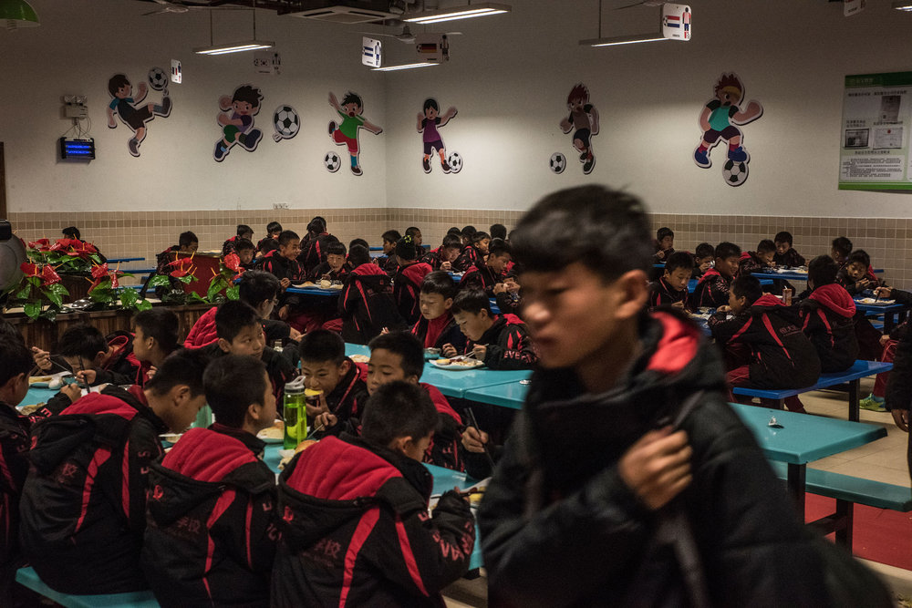 Students of the Evergrande football school having breakfast at the school's canteen decorated with drawings of football players.