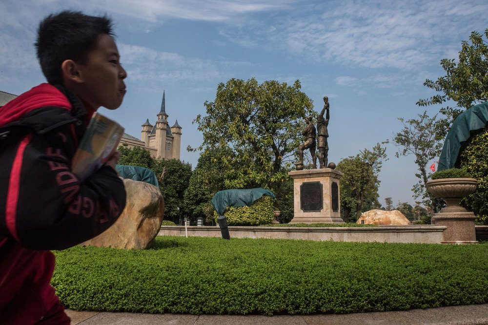 A student book in hand running to class through Evergrande football school park decorated with the statue of a player with the world cup trophy in hands.