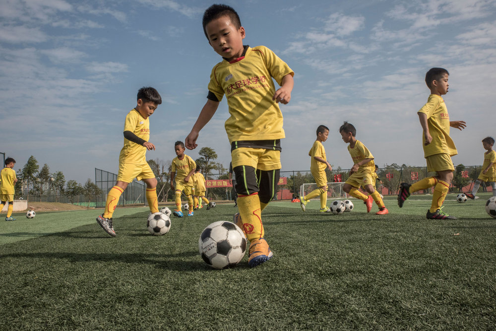 Students of the Evergrande football school practicing their dribbling.