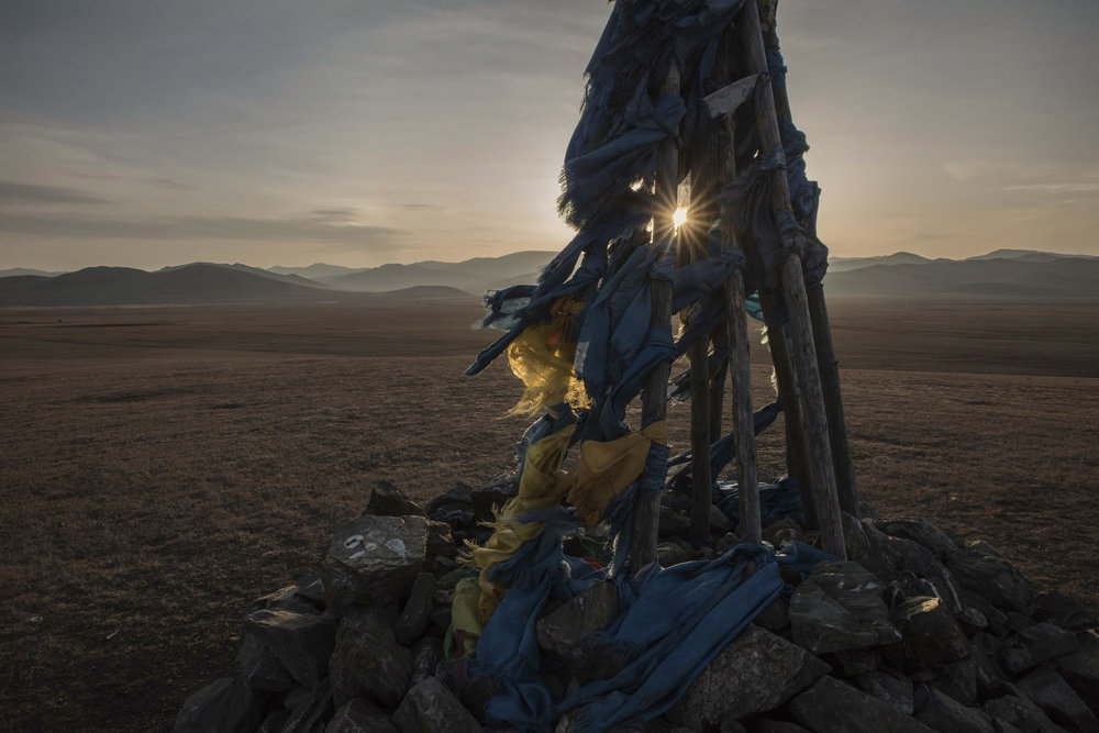 A wooden ovoo adorned with blue khatas at sunset in the Mongolian grassland. Ovvo are shamanic shrines usually situated along roads or on top of mountains and used by mongols to pay they respects to the spirits by walking around them and throwing vodka or milk to them.   Shamanism is an adoration of nature in all its forms. As the Mongolian environment has become threatened by unchecked mining, and air pollution, the new shamans have turned environmentalists, protectors of both the Mongolian culture and country's nature.