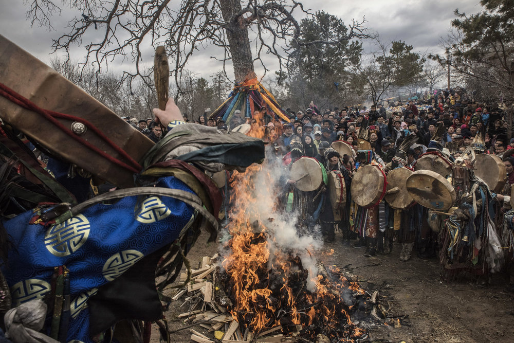 Shamans have gathered in circle around a wood fire, beating sheepskin drums to call the spirits during a celebration of spring in northern Mongolia.