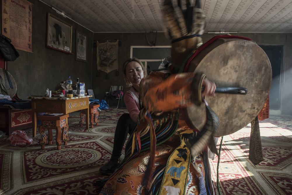 Enkhoyun, daughter of master shaman Byambadorj, helping Suhe, a novice shaman, as he is getting into a trance.