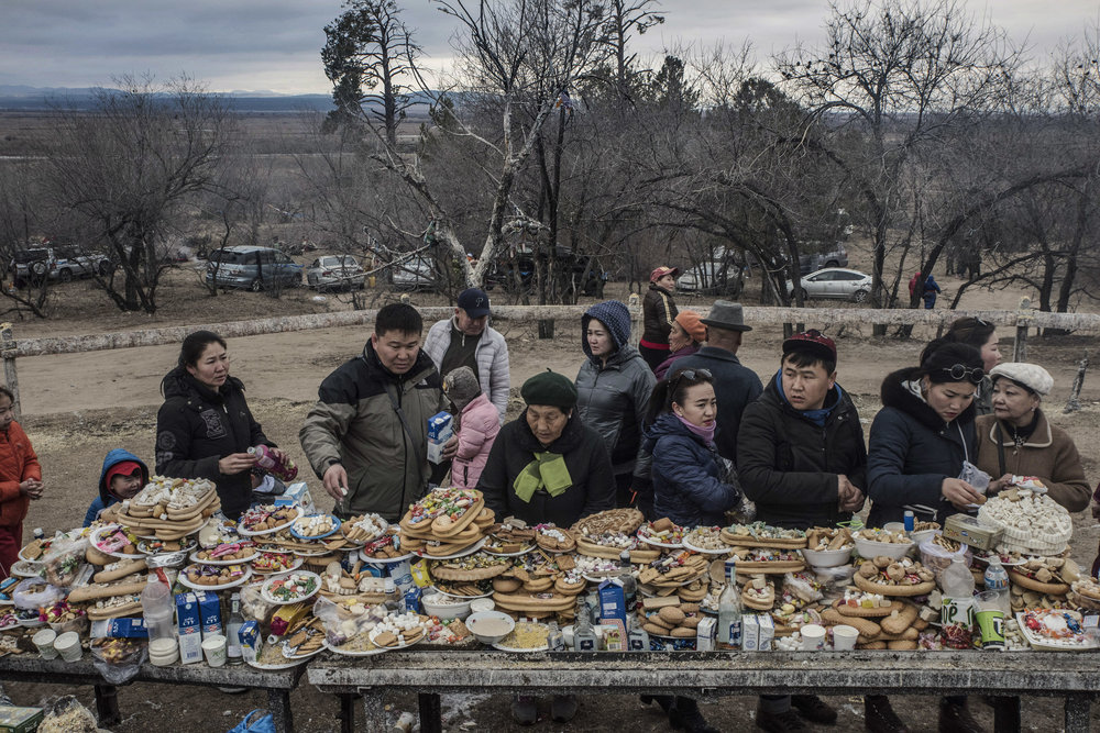 Participants to a shamanic celebration of spring have placed offerings of cake sweets, milk and vodka on an altar as offering to a sacred tree believed to have strong powers.