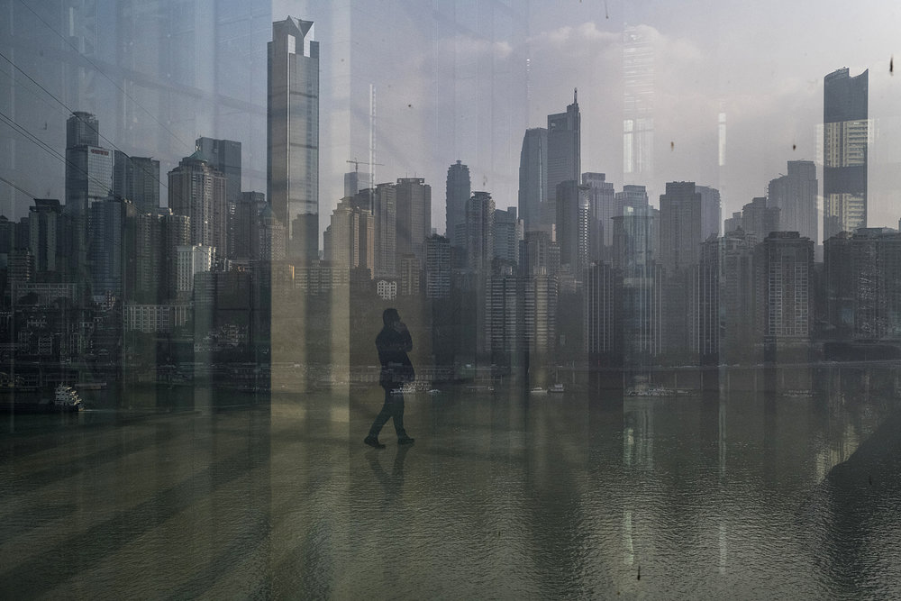 A man reflects on window overlooking Chongqing skyline, seen from the megalopolis new business district.