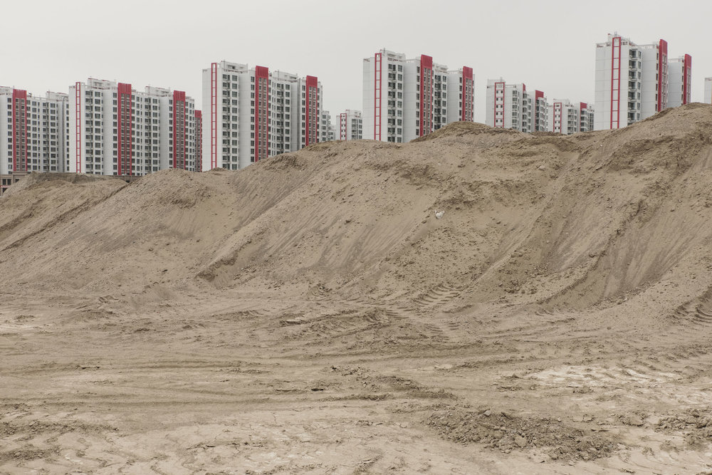 Lanzhou New Area, a city emerging from the sands. The construction of the city started in 2012, and involved levelling hundreds of barren hills. As of 2017 only a few thousands inhabitants had moved in. The city has been planned to harbour 1 million inhabitants by 2020.   China's urbanisation has lead to the creation from scratch of dozens of new cities, few of which have been successful.