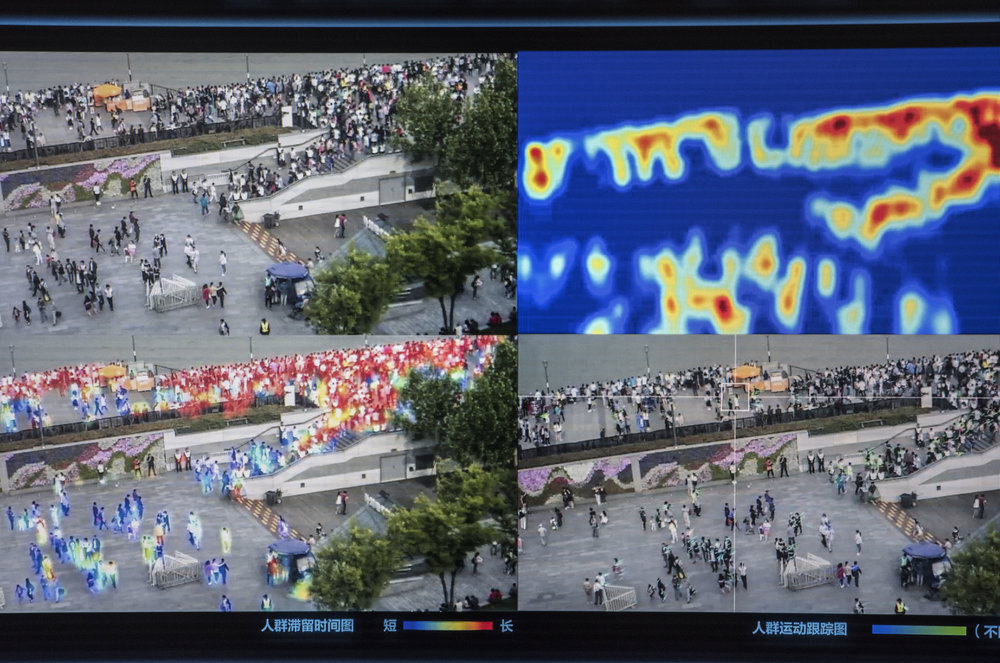 """Screen capture of a video footage showing Sensetime crowd monitoring system. It allows to measure a crowd density (the color patches on the image), as well as the identification of """"abnormal"""" behaviours."""
