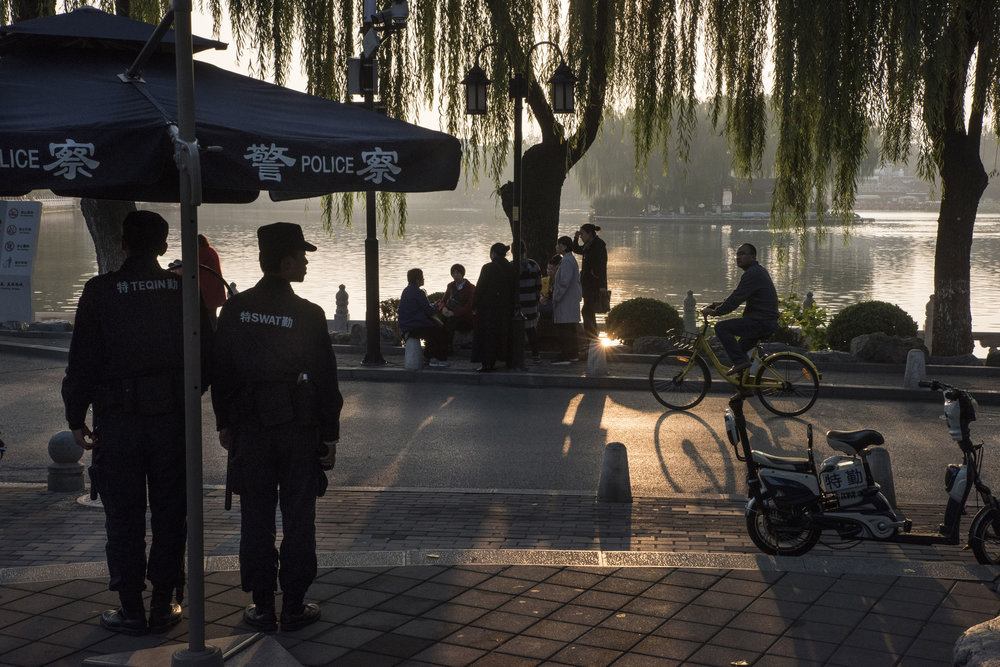 Police standing guard by Houhai Lake in Beijing.  For security, China relies on lo-tech, as well as high tech. Chinese cities use different levels of policing : community patrols run by private citizens organized at the neighborhood level, private security firms, city police, and armed police (under the authority of the People's Liberation Army).