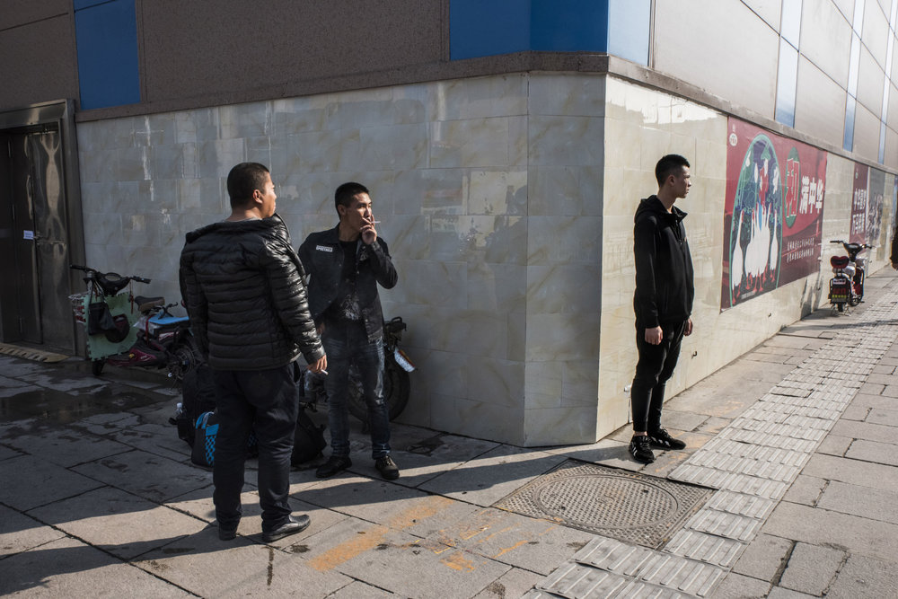 A plainclothes security (right) standing guard on a commercial street in the neighbourhood of the Great Hall of the People where China's Communist Party 19th congress is taking place.