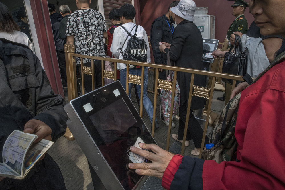 Visitors to Tian An Men square having their ID scanned at a security check. The machines are equipped with cameras for facial recognition.