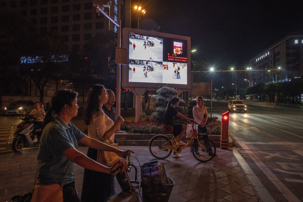 In Xiangyang, at a crossroad equipped with monitoring cameras linked to facial recognition technology, an outdoor screen displays photos of jaywalkers alongside their name and I.D. number. The idea is to embarrass offenders into compliance.