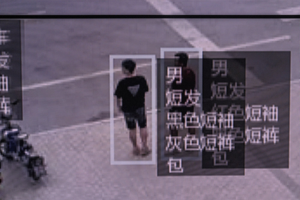 Screen capture of a CCTV footage showing human recognition recognition software in use, at the showroom of Face++ headquarters in Beijing. In this case the software describes a pedestrian : short hair, black t-shirt, grey short, carrying a bag.