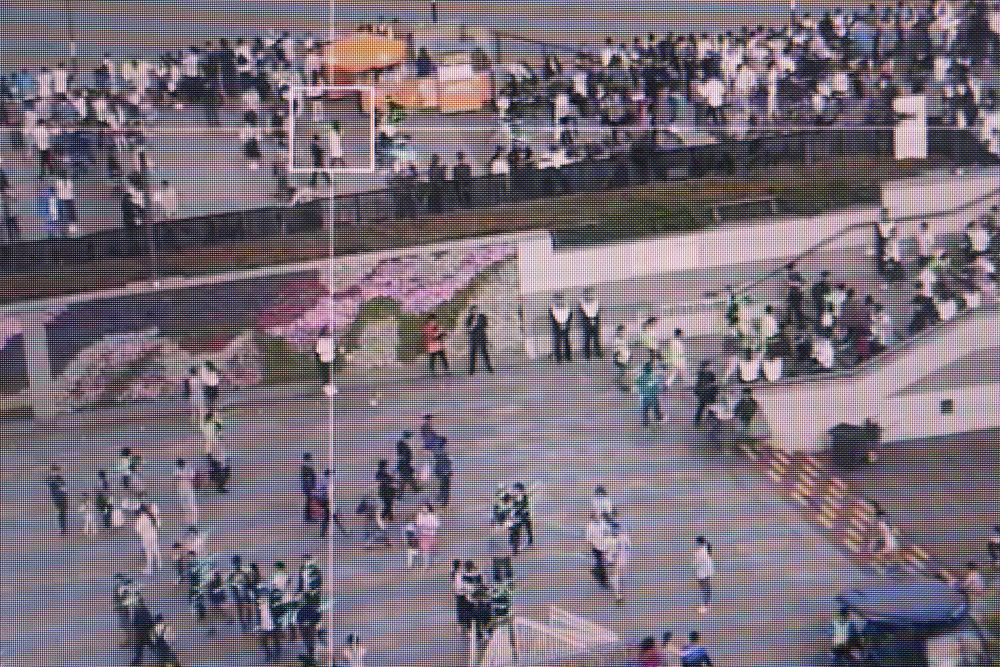 """Screen capture of a video footage showing Sensetime crowd monitoring system. It allows to measure a crowd density as well as the identification of """"abnormal"""" behaviours."""