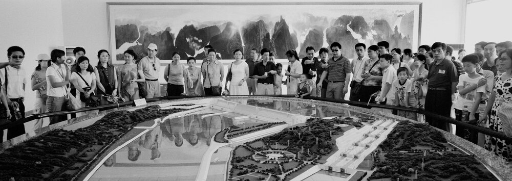 A group of Chinese tourists are looking at a model of the three gorges dam. In spite of the controversy surrounding it the dam has become a tourist sight and an object of pride for many Chinese.