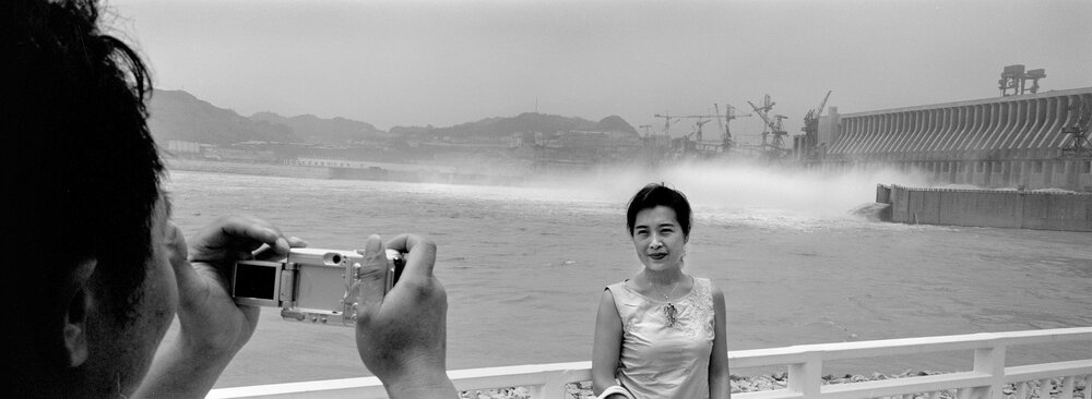 A tourist posing for a picture in front of the Three Gorges Dam. The dam has become a tourist attraction and an object of National pride, in spite of the controversy surrounding its construction.