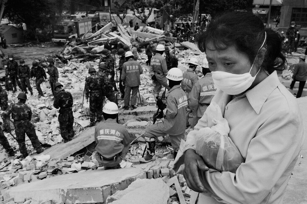 A mother waiting for the rescuers to find her 15 years old daughter in the ruins of Beichuan middle school.