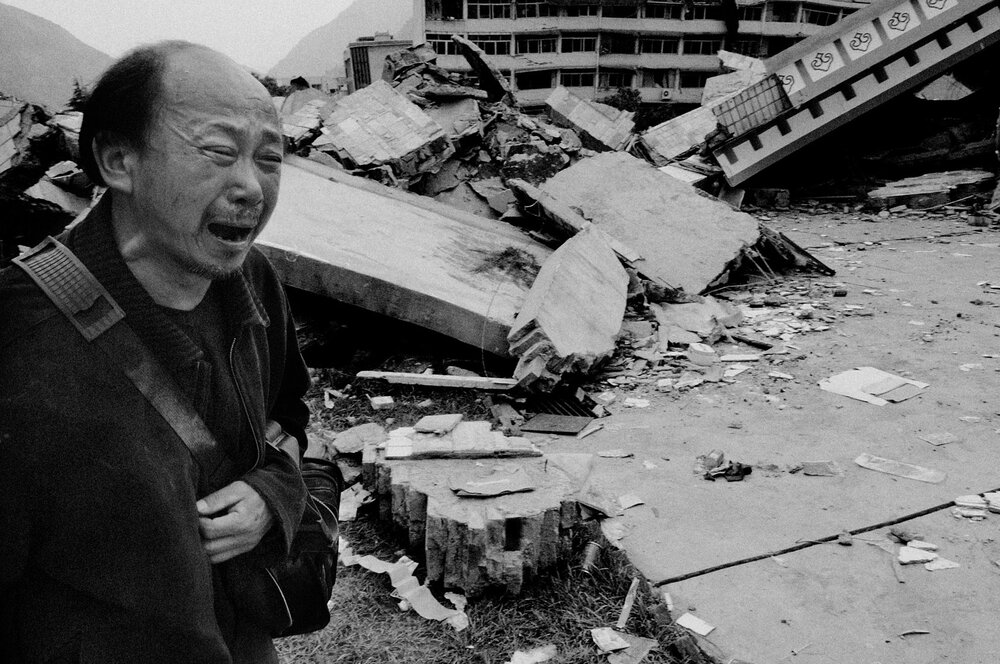 A man wandering through Beichuan in ruins, crying.