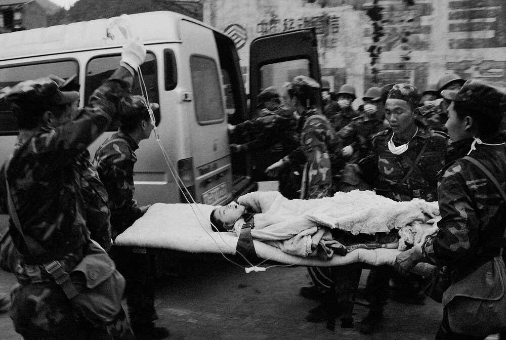 A survivor from the earthquake is brought in by P.L.A. soldiers.