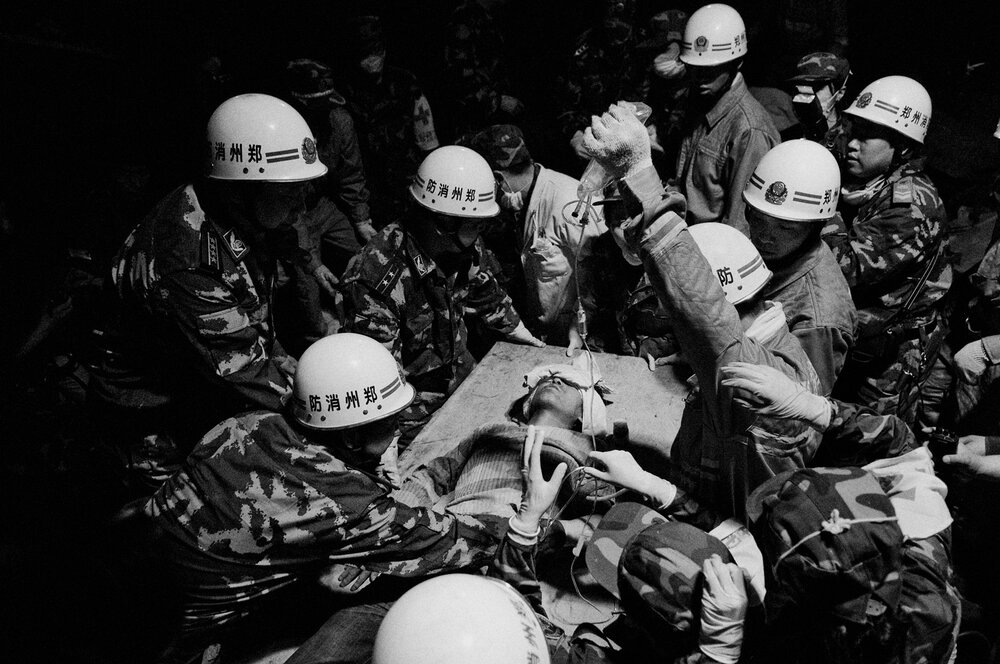 Li Qing Song is being taken out of the building alive by a team of rescuers from Henan province. He has spent 104 hours buried under the debris of the workers club where the eartquake caught him.