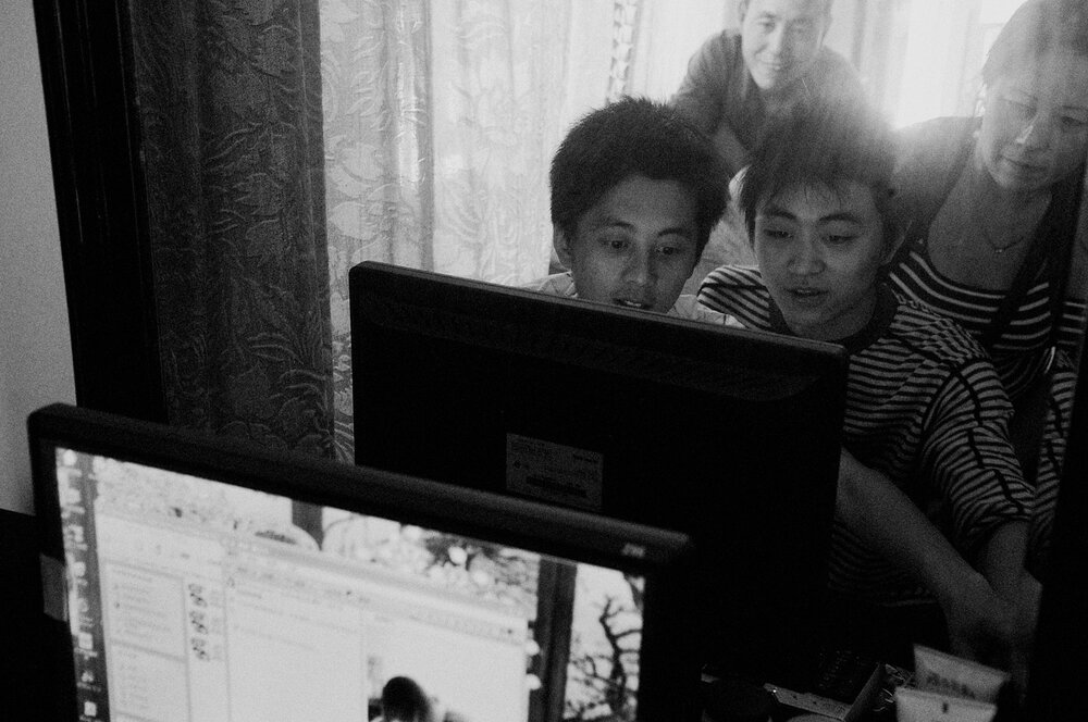 Back to life, back to MSN. 36 hours after his rescue and spending 4 days trapped in the debris of a collapsed building, Li Qing Song (right) his back with his family. He is chatting online with a net friend next to his brother (left) his aunt and his dad (behind).
