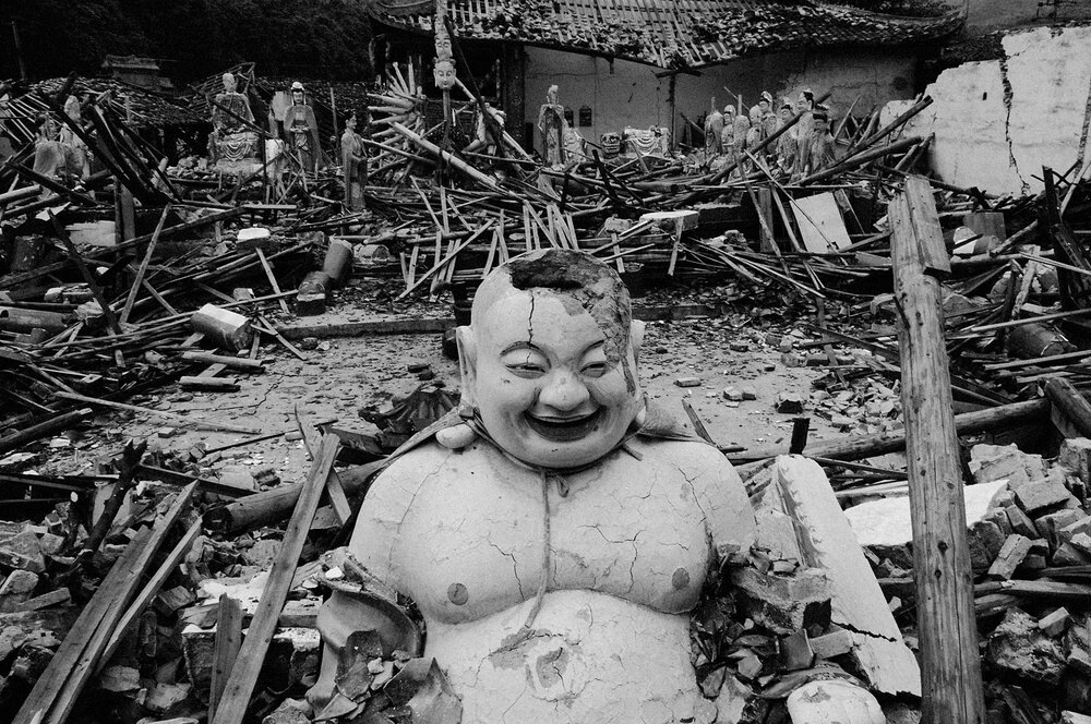 At Longju Temple the Buddha keeps smiling amid the ruins.