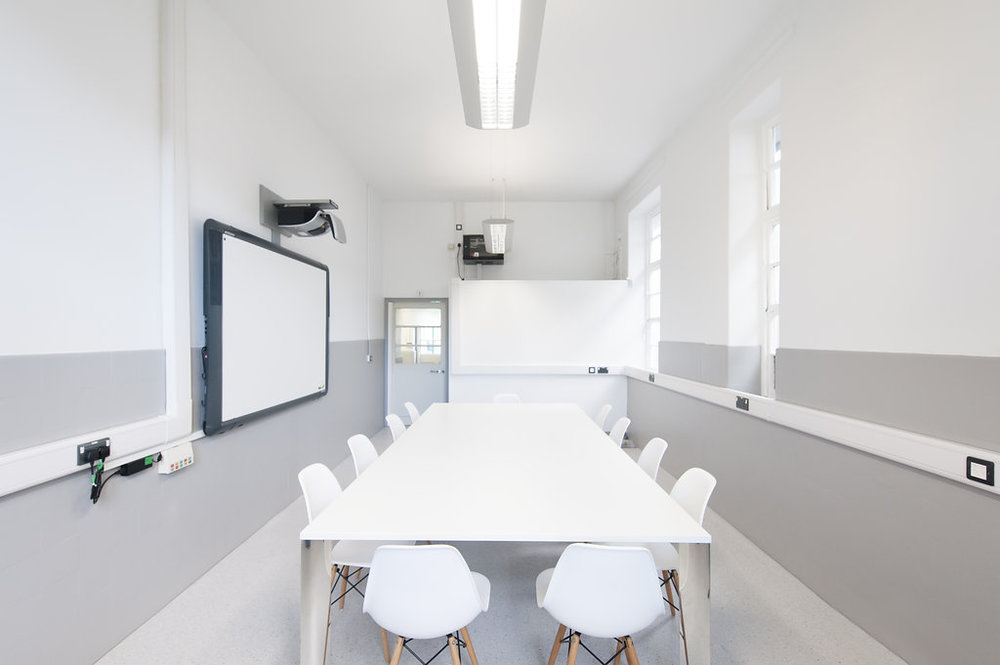 MEETING room : interactive whiteboard, board table, and seating for up to 12 people.