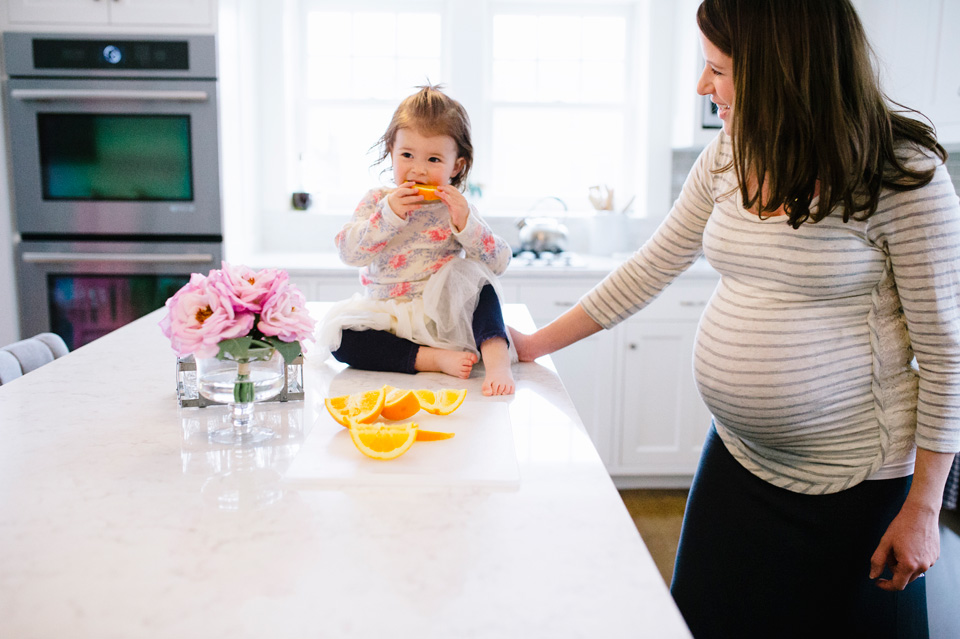 mother and daughter eat oranges in beautiful modern kitchen
