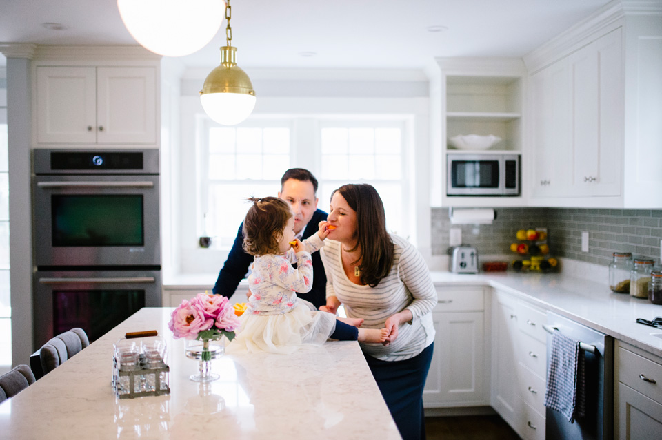 family eating in beautiful modern kitchen with toddler