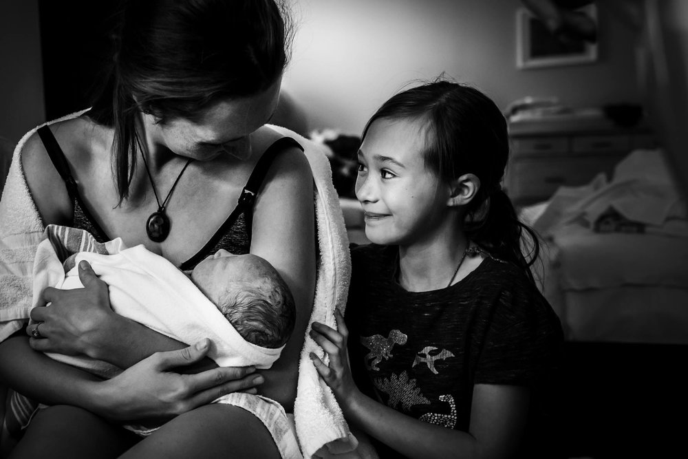 This big sister watched with pride as her mom birthed her baby brother into the world. Image by  Monet Nicole - Birthing Stories.