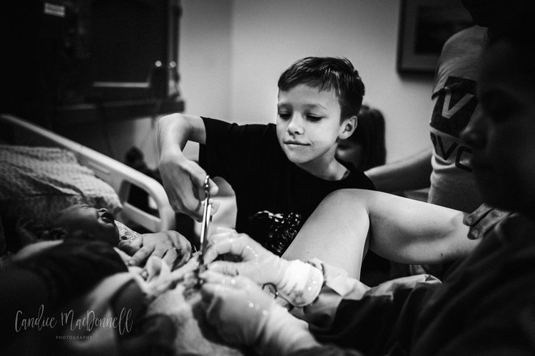 Older brother helps cut the cord. Lovely image by Candice MacDonnell Photography.