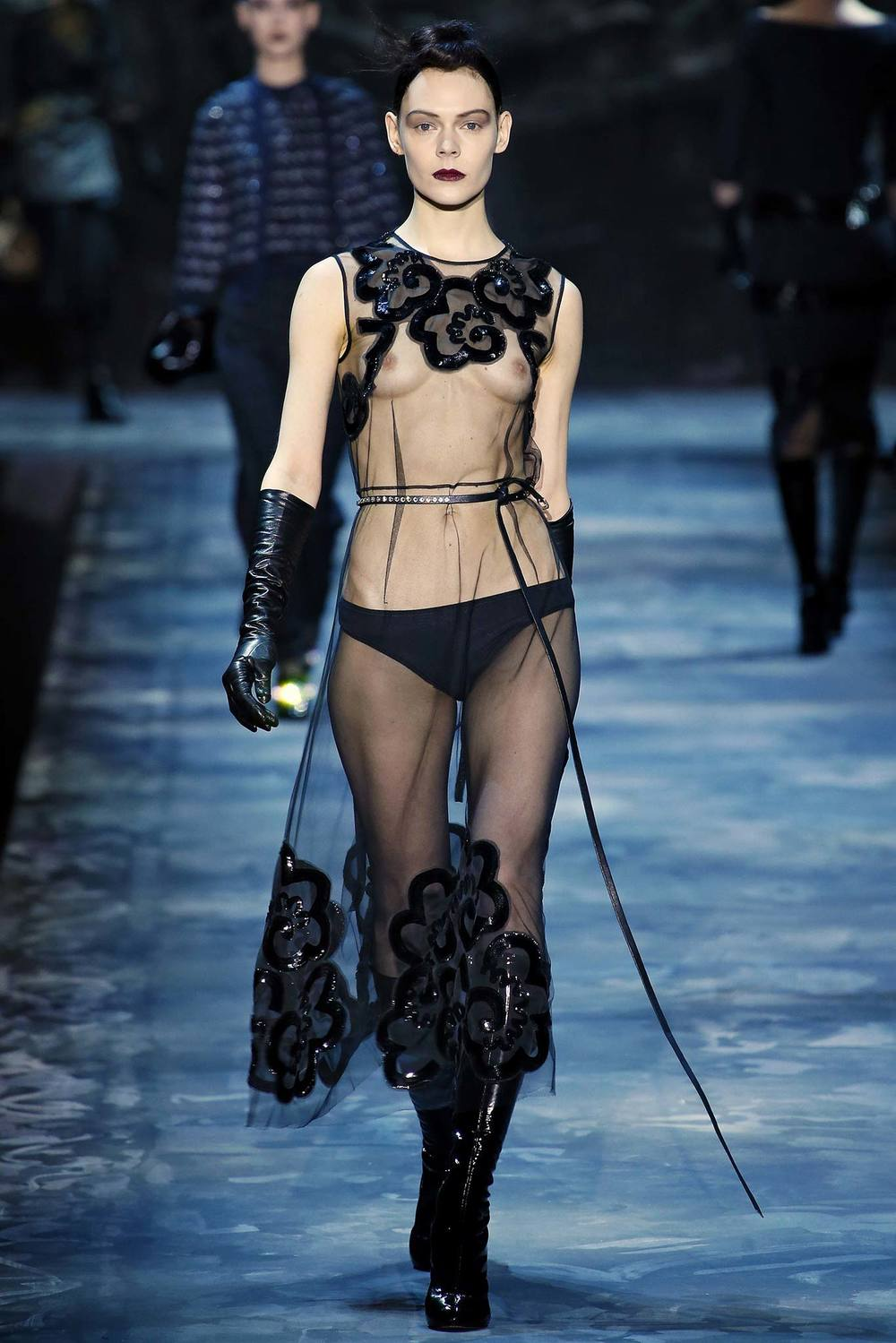 Featuring elbow-length black gloves, sheer clothing, 'leash-like' belt, patent boots.