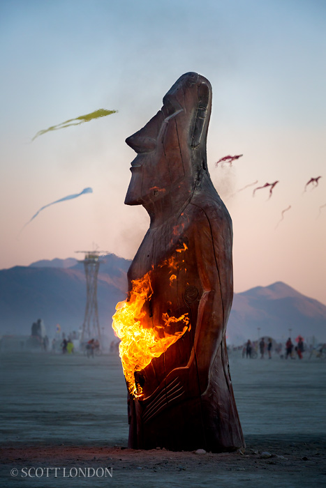 "An art piece called ""Annunaki Watch"" being burned from the inside out by its artist."