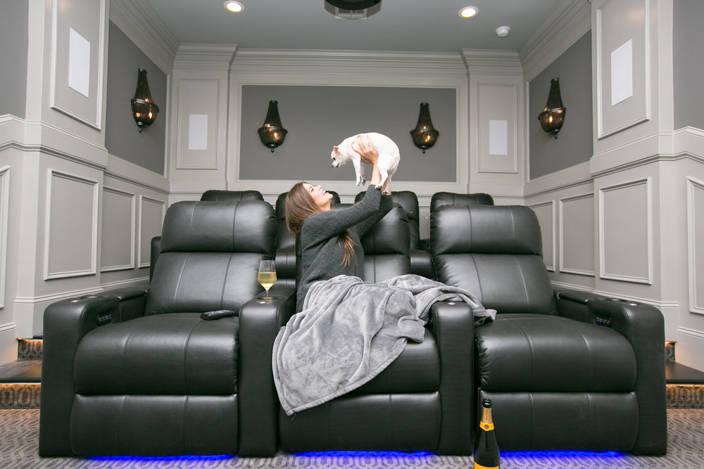 Designer Jacquelyn Lindsey in finished home theatre design with client's puppy, Chloe