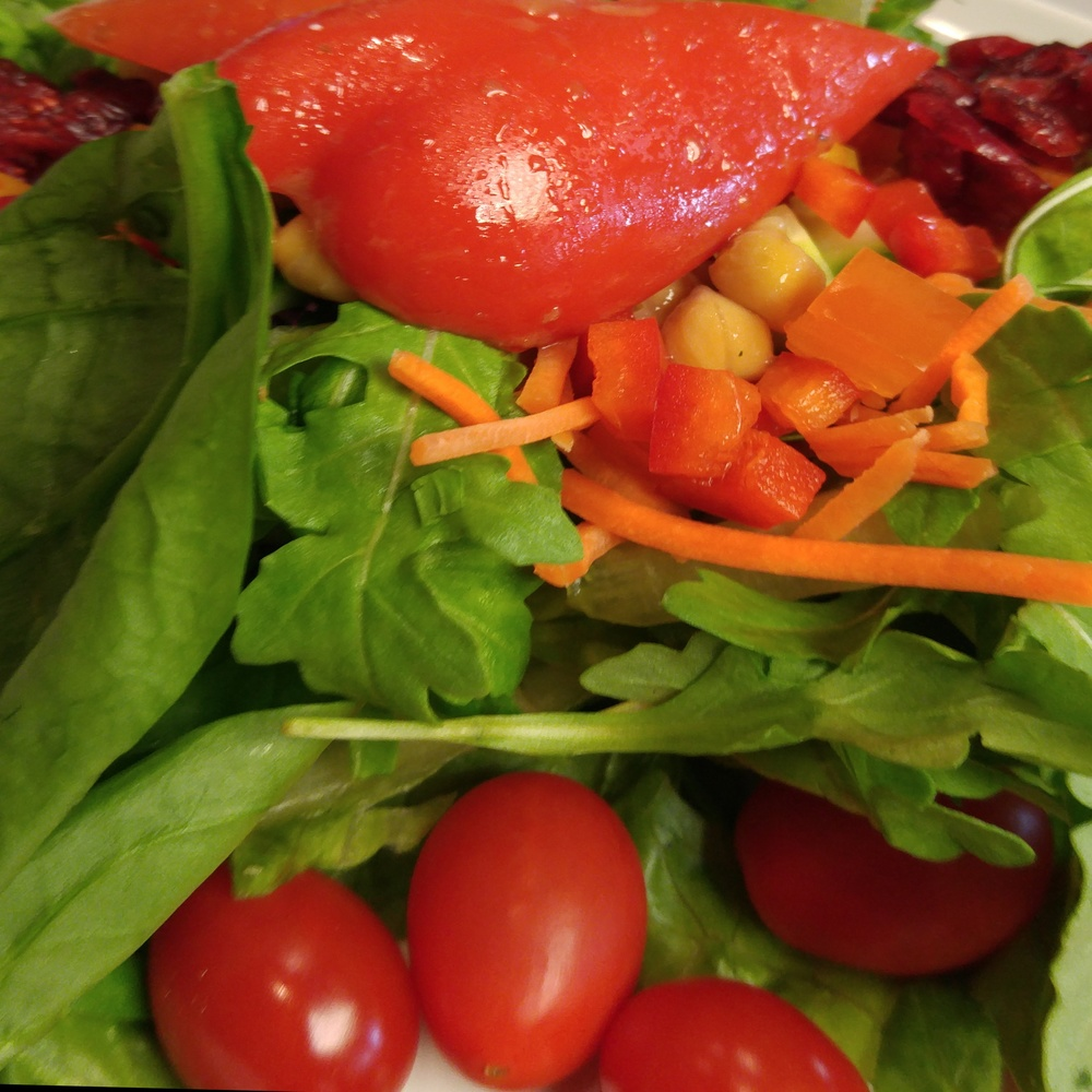 Arugula salad, chickpeas, tomatoes, shredded carrots, mixed veggies, beets, dried cranberries, pickled peppers