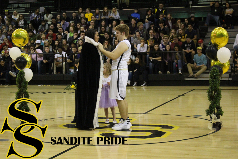 Senior Jacob Taber places the robe and crown on Scott.