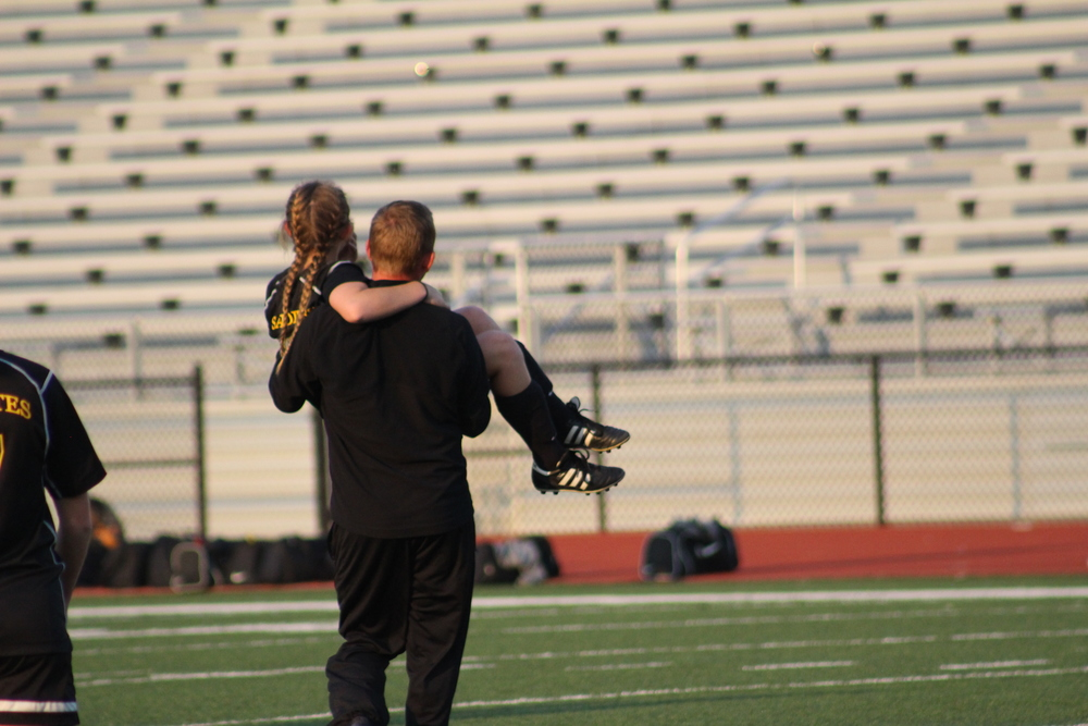 Behrens carries an injured player off the field.