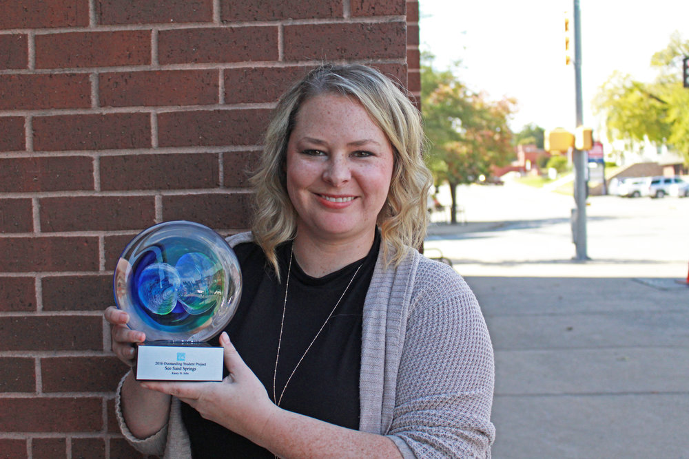 City of Sand Springs Marketing and Special Projects Manager Kasey St. John poses with her OKAPA award.