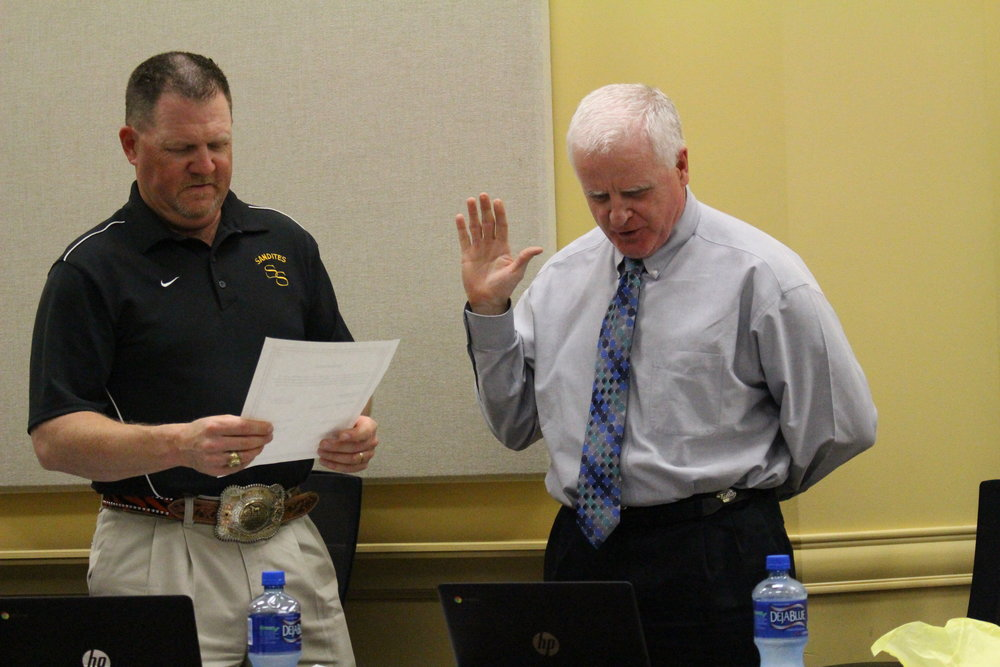 Board member Mike Mullins recites the Oath of Office.