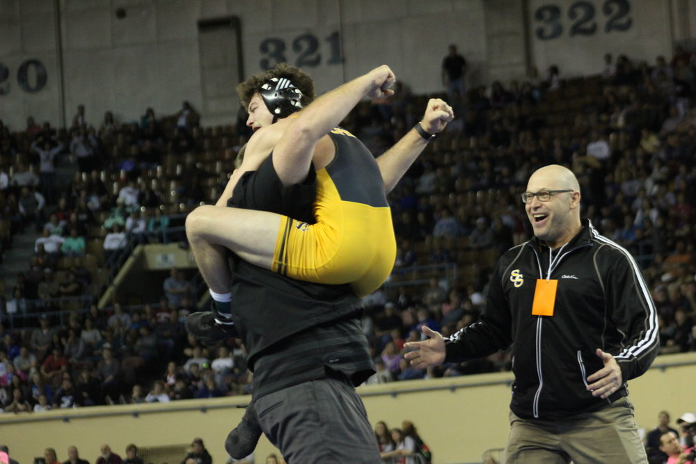 Jack Karstetter celebrates his first State Championship win with coaches Dustin Kinard and Jay Fleischman.