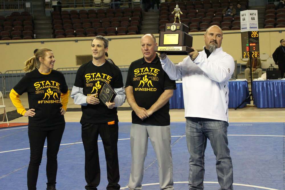 Sand Springs Athletic Director Rod Sitton presents the State Tournament trophy to CPHS Principal Stan Trout, Head Coach Kelly Smith, and Superintendent Sherry Durkee.